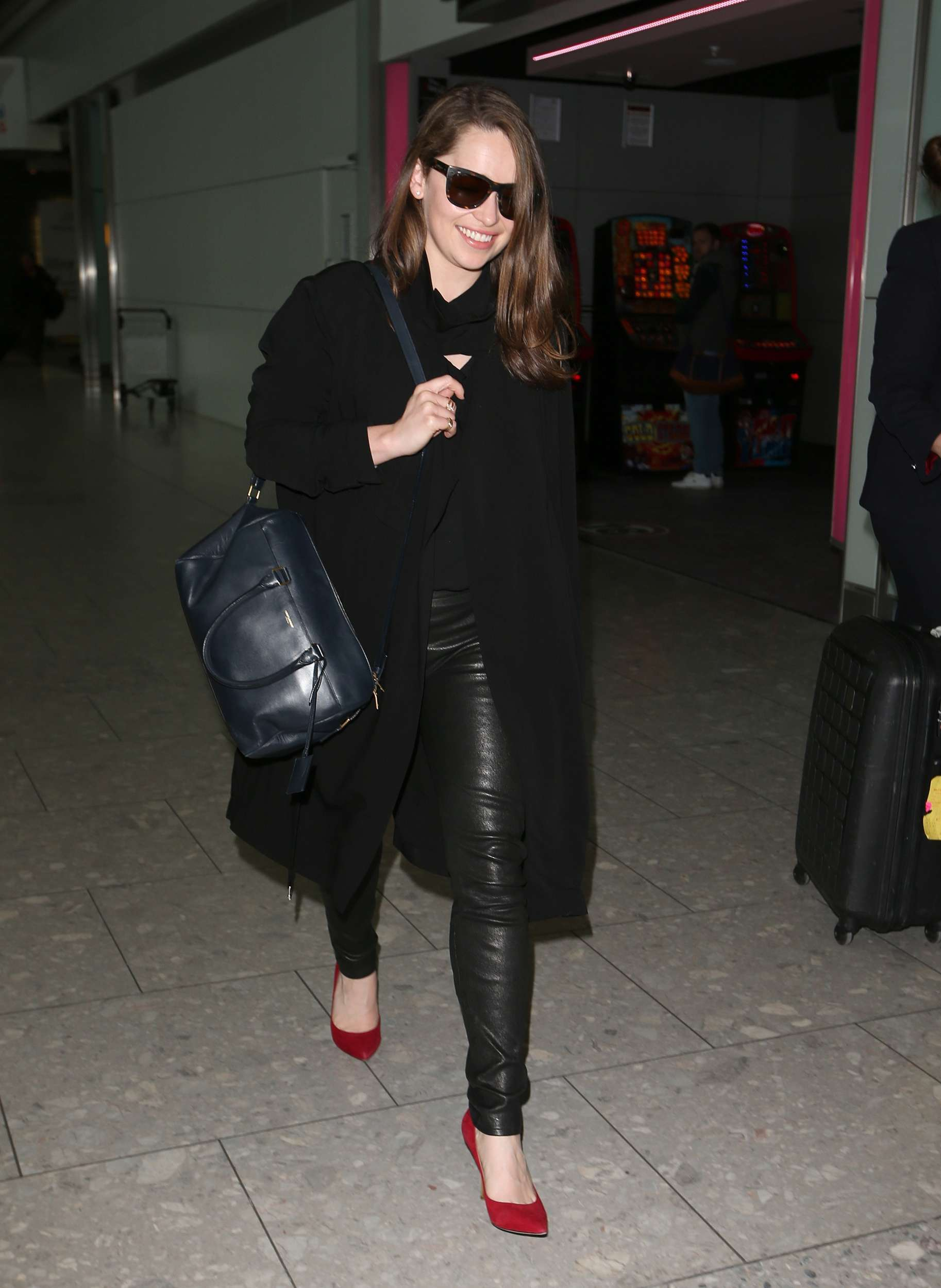 Emilia Clarke Walks through Heathrow Airport